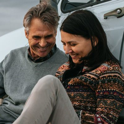 Two people sitting beside a car