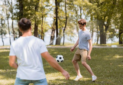 Teenager and adult playing football in the park