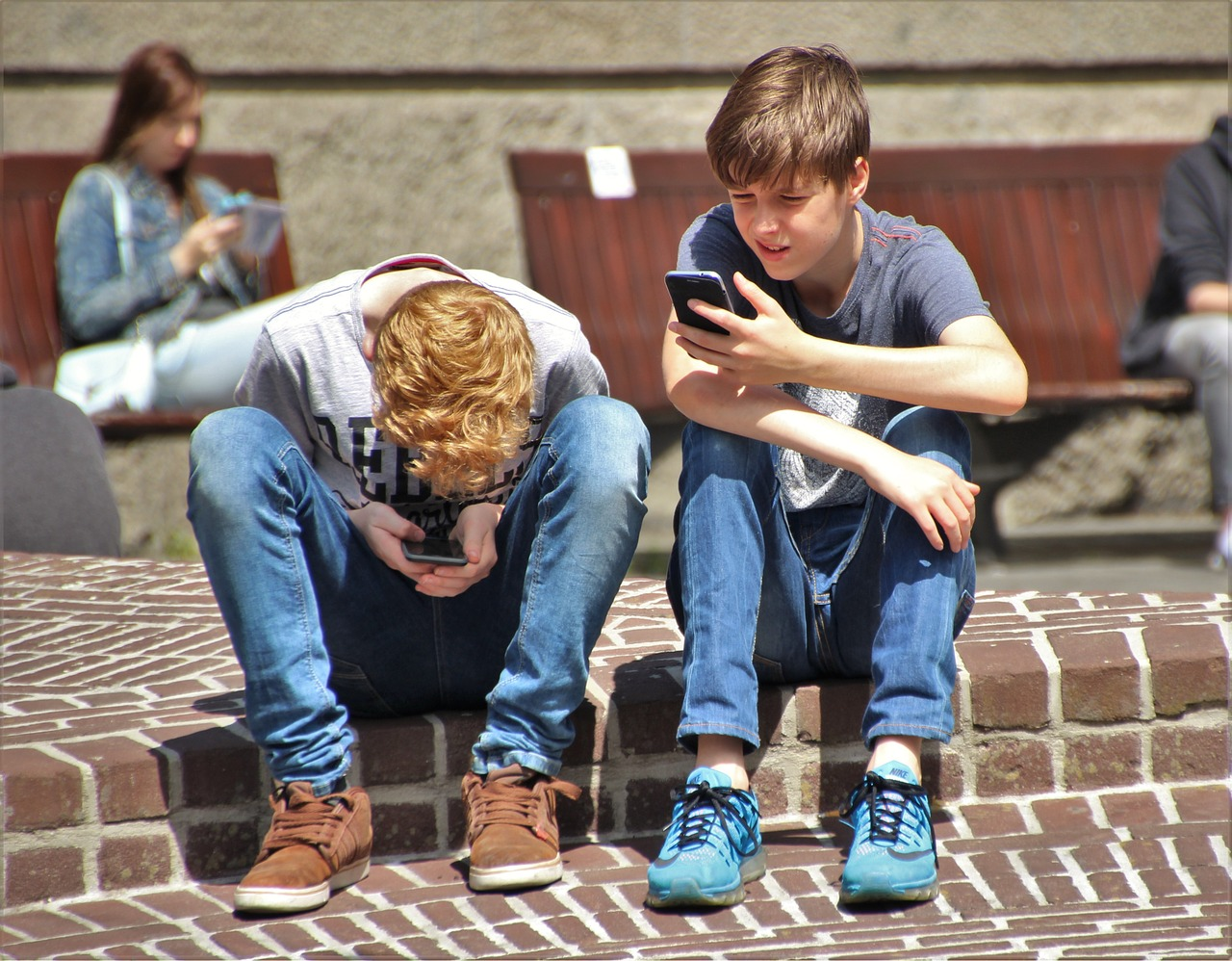 two boys with mobile phones